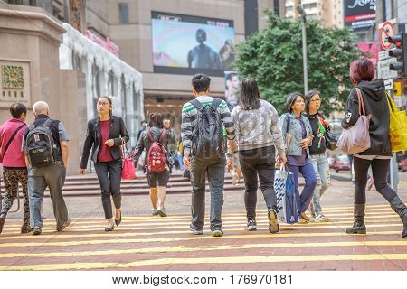 Hong Kong, China - December 6, 2016: Causeway Bay is one of the most attractive areas for tourists and business people and good for shopping. Asian couple crossing the Times Square intersection