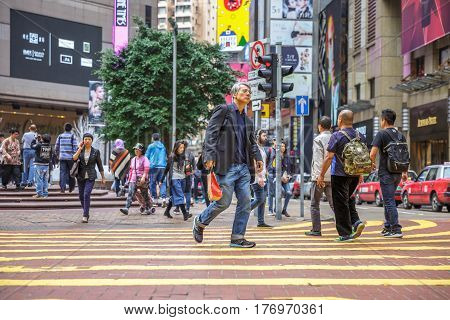 Hong Kong, China - December 6, 2016: Asian elegant busy people crossing the Times Square intersection of Causeway Bay one of the best place for luxury shopping.