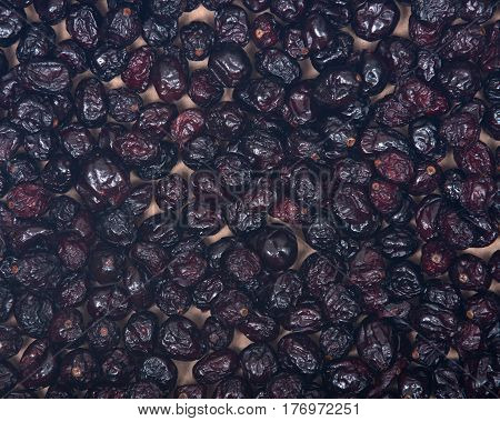 Whole organic dried cranberries on wooden vintage tray like art background