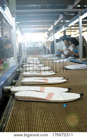 worker making shoe sole in production line of footwear industry with lens flare technic