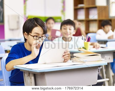 asian elementary schoolboy looking with curiosity at a tablet computer held by his classmate focus on the boy in foreground.