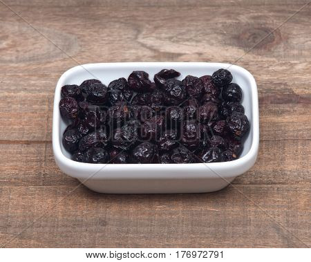 Whole organic dried cranberries on wooden vintage tray background