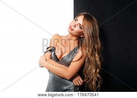 Young sexy woman in evening dress standing in a contrasting background. Strap dress fell down and bared beautiful shoulders.
