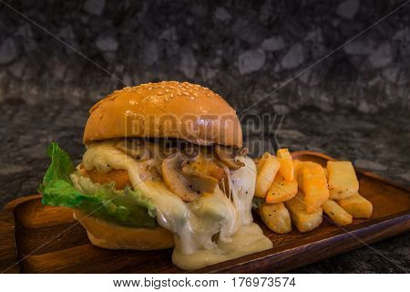 Close-up of Cream mushroom sauce Burger with French fries on wood plate.