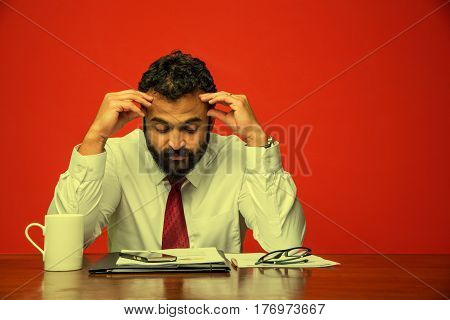 frustrated indian young businessman with beard showing sad expressions in the office at computer table