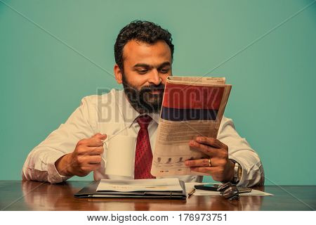 photo with special effect showing indian young businessman reading newspaper while having coffee in the office, asian businessman enjoying coffee while reading news publication