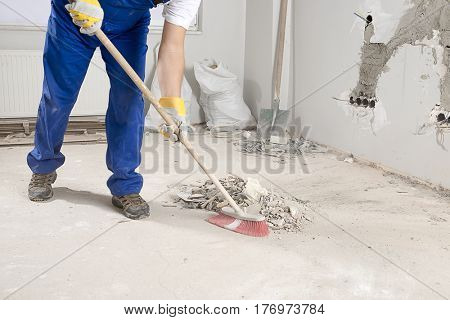 Manual worker sweeping rough rubble at construction site using broom.