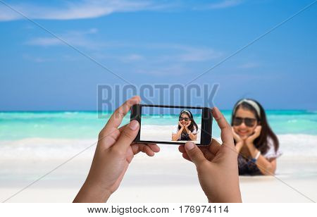 Smartphone photographing Asia woman in Tropical beach Similan Island Koh Ta Chai Andaman Sea Thailand
