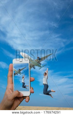 Smartphone take a photo of girl relaxing and see airplane landing on the beach in summer day