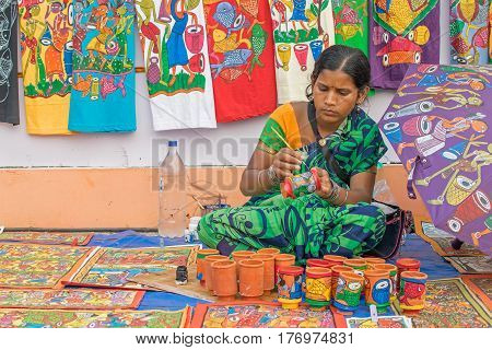 Kolkata West Bengal India - 28th November 2015 : Woman hand coloring pen stands made of clay handicrafts on display during the Handicraft Fair in Kolkata. Biggest handicrafts fair in Asia.
