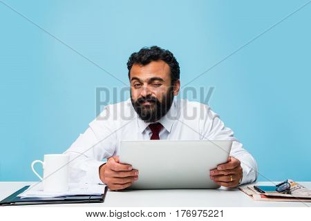 Bearded indian businessman holding tab or tablet pc with happy look while sitting at office table, asian business person holding touch pad