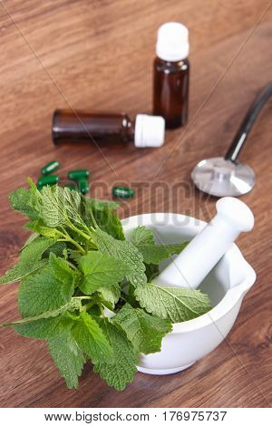 Lemon Balm In Mortar, Stethoscope And Medical Capsules, Choice Between Pills And Alternative Medicin