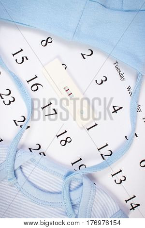 Pregnancy Test With Positive Result And Clothing For Newborn On Calendar, Expecting For Baby