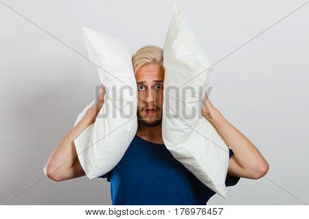 Sad Man Closing Ears With Pillows