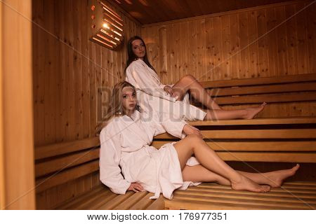 a group of young beautiful women enjoys relaxing in the sauna in the modern spa salon
