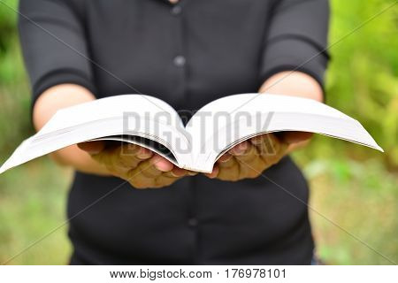 Hands of person hold the book on nature background