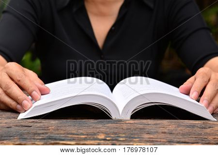 person read the book on wooden table