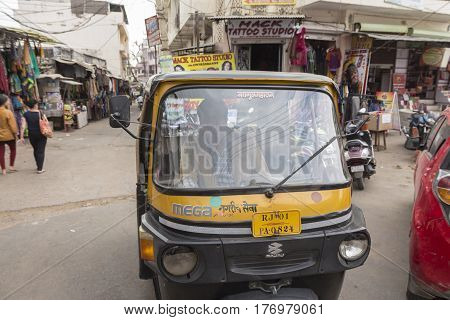 PUSHKAR INDIA-OCT 30 : yellow autorickshaw and driver in Pushkar city on october30 2014 india. autorickshaw is name of taxi car in india