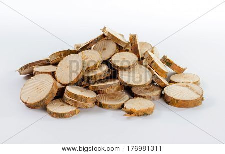 Pile of many little round pieces of sawn pine branches on white background