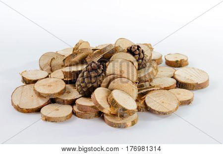 Stack of little round pieces of sawn pine branches and two pine cones on white background