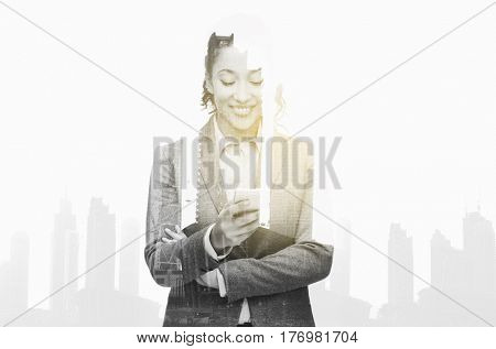 business, people and technology concept - smiling african american businesswoman looking at smartphone over city buildings and double exposure effect