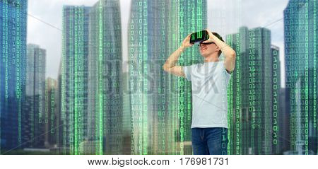 modern technology, entertainment, cyberspace and people concept - happy young man with virtual reality headset or 3d glasses over city skyscrapers and binary code background