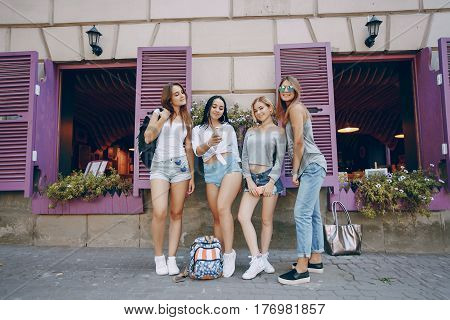 Four beautiful girls in stylish clothes in summer city