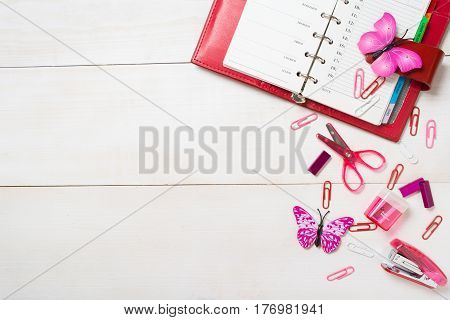 Planning concept for girl or woman with red organizer and pink stationary on the white wooden table decorated with butterfly