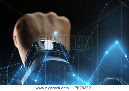 business, people and technology concept - close up of businessman hand with smartwatch and diagram chart virtual projection over black background