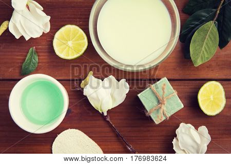 beauty, spa, body care and  natural cosmetics concept - close up of bowls with citrus body lotion, cream and soap on wooden table