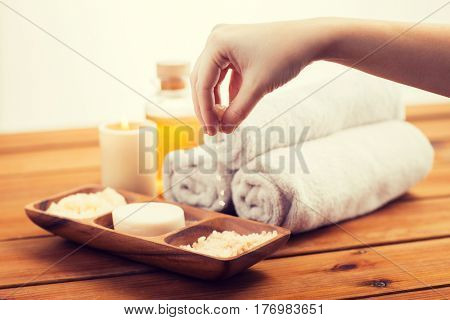 beauty, spa, body care and natural cosmetics concept - close up of hand pouring himalayan salt in wooden bowl with soap, scrub and bath towels on table