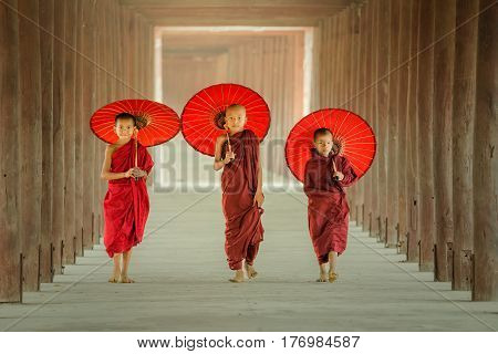 Myanmar The three novice walking on the pagoda and holding red umbrella in MandalayMyanmar.
