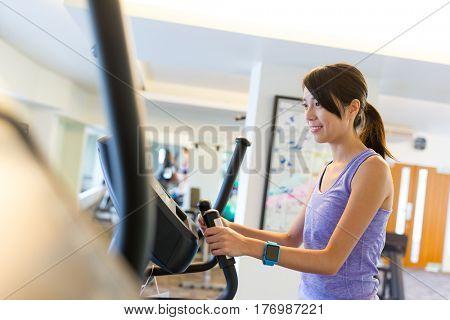 Woman training on Elliptical machine at gym