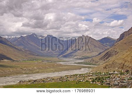 View over the Ancient Town of Kaza nestled in the Spiti Valley in the High-Altitude Mountain Desert amidst Snowcapped Summits in the Himalayas
