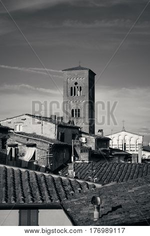 Tower of Chiesa San Pietro with roofs of historic buildings in Lucca, Italy.