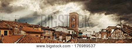 Tower of Chiesa San Pietro with roofs of historic buildings and sun ray in background panorama in Lucca, Italy.