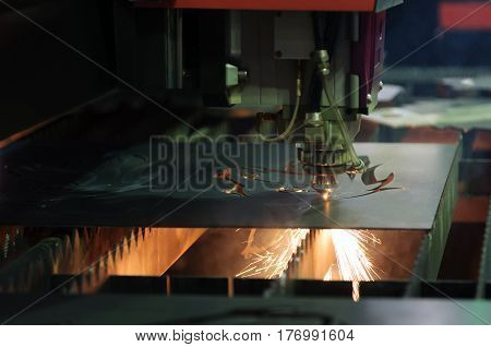 The CNC laser cut machine while cutting the sheet metal with the sparking light.The hi-precision sheet cutting process by laser cut