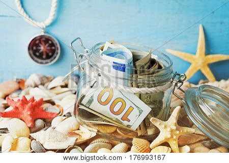 Money in glass jar on seashell background. Savings for summer holidays vacation travel and trip.