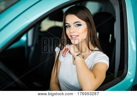 Smiling woman driving car attractive girl sitting in automobile.