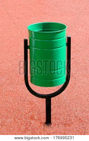 Green garbage urn on an artificial covering