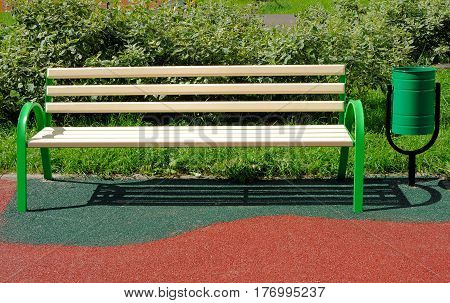 Bench and urn on an artificial covering of playground