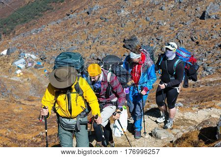 Group of People dressed in bright sporty Clothing walking up on steep Mountain Trail with mixed rocky and grassy terrain carrying Backpacks and using hiking Sticks.