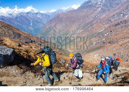 Group of People dressed in bright sporty Clothing walking up on steep Mountain Trail with mixed rocky and grassy terrain carrying Backpacks and using hiking Sticks majestic Peaks View on Background.