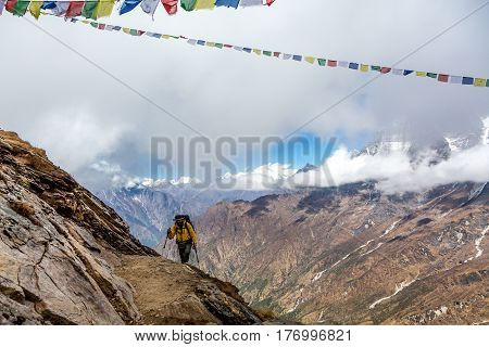 Man in yellow sporty Jacket with Backpack and using walking Sticks approaching to Mountain Pass in Nepal Himalaya. Buddhist Prayer Flags strained between Rocks. Valley View low clouds on Background