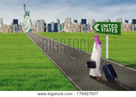 Back view of Arabian businessman walking on the highway with United States text on the signpost while carrying a suitcase and a briefcase
