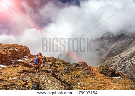 Two Mountain Hikers walking on Trail with mixed rocky and grassy surface carrying Backpacks using walking Sticks massive Clouds and shining Sun on Background