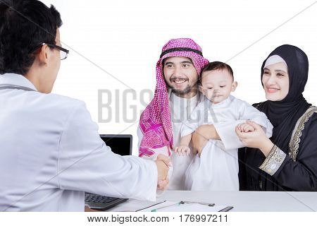 Arabian family handshakes with pediatrician while sitting in the studio isolated on white background
