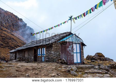 Mountain Hut in Nepal Himalaya Stone Building with Shop and Shower decorated by traditional Buddhist Prayer Flags