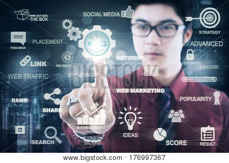 Picture of a young Asian businessman pressing a virtual SEO button on the digital screen. SEO concept