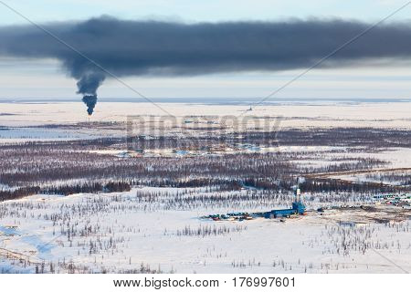 Aerial view of oil rig at an oil field in Western Siberia in the winter day. Black smoke rising from Gas-jet burner for gas flaring which is located near the rig.